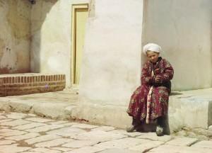 Menino sentado no pátio da Mesquita Tillia-Kari, Samarcanda (atual Usbequistão), 1910.